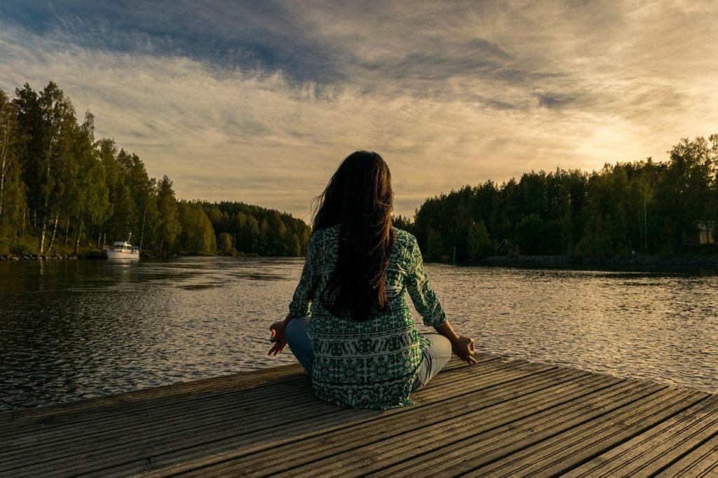 jeune fille sur un quai faisant du yoga